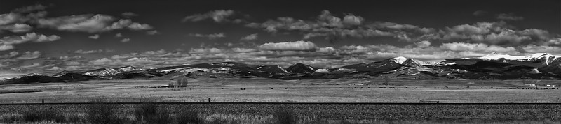 25 May 21As most of you likely know MT is known as the The Big Sky state. It doesn't take any imagination to understand why if you've ever driven across the state via I-90 or just spent some time visiting. For today's Black and White Tuesday I'm sharing a shot of how the area frequently looks about an hour west of Butte. I find the views beautiful but my bride has a decidedly different opinion. No matter when we travel through this area there is always a show of clouds overhead, much like the eastern part of WA state when traveling via I-90. We've made the journey cross country probably 6 times via this freeway and every time it has been a wonderful trip. With nice white textured clouds, grain fields of yellow, deep brownish plants lining the railroad bank, and a definitely blue sky, I felt this setting perfect to show off in monochrome.  This is a 7 frame pano and other than some required cropping to correct for my not holding the camera straight, and a small amount of dodging and burning, this is what the camera captured. Approaching Adams  Nikon D500; 18 - 200; Aperture Priority; ISO 200; 1/1,600 sec @ f / 9.