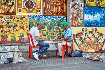 Two street vendors in Santo Domingo, Dominican Republic, play games in between their wares to pass the time.