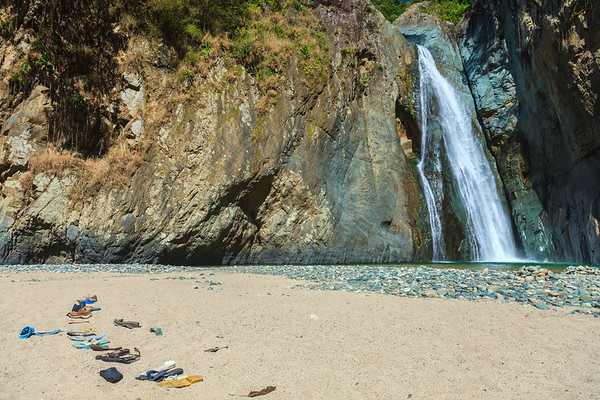 A collection of shoes line the beach near Salto de Jimenoa I,  one of Jarabacoa's famous waterfalls