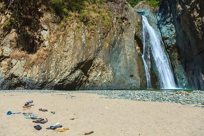 A collection of shoes line the beach near Salto de Jimenoa I,  one of Jarabacoa's famous waterfalls