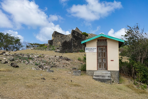The Belvedere Post Office, Carriacou.  Ruins of an old stone church in the background.