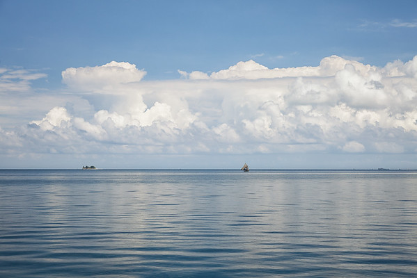 A bois fouilles sailboat with fishermen aboard tries to find some wind in the glassy sound between Ile A Vache and mainland Haiti.