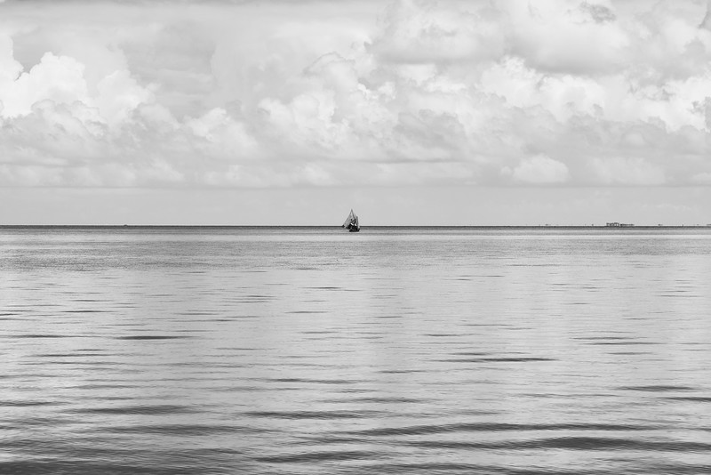 A bois fouilles sailboat on the glassy water between Ile A Vache and mainland Haiti.