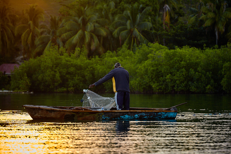 Fisherman laying out his morning nets in the harbor