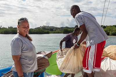 Many old sails have been donated to the fishermen on Ile A Vache, Haiti.  Locals are offloading them from the big boat to their small boat to take ashore.