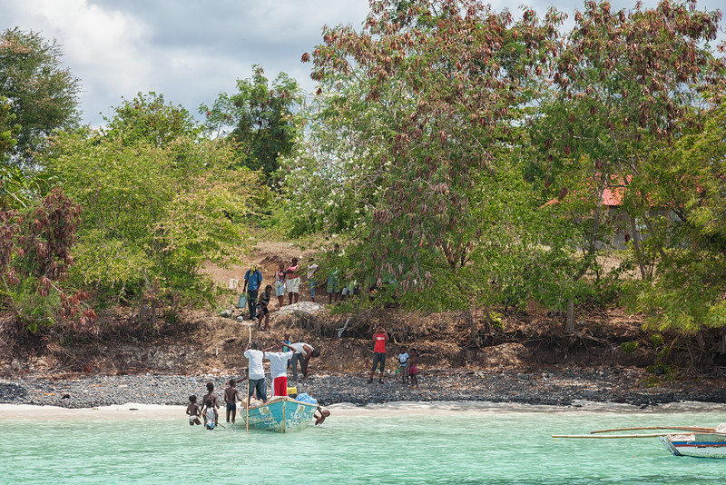 Boys watching the older guys offload supplies onto the beach in La Hatte, Ile A Vache, Haiti.