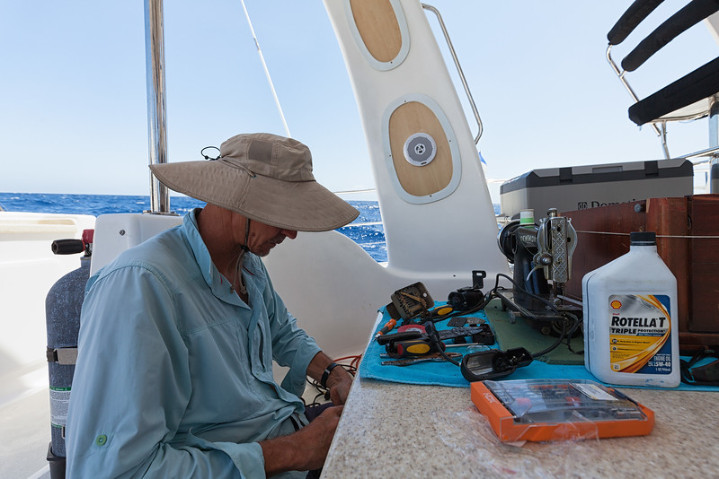 Jan repairing one of the sewing machines during our sail.  These will be donated to the Haitians.