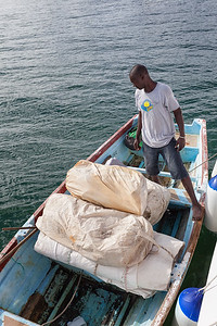 Silnor inspecting the old sails that have been offloaded into his boat before taking them to shore to hand out to fishermen.