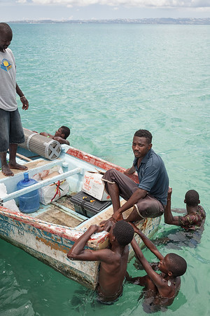 Boys cling to the boat bringing supplies ashore from the larger sailboat that brought them there.