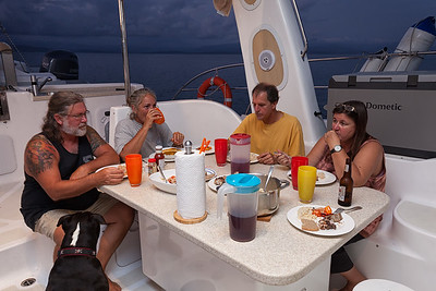The crew eating grilled tuna that was caught on the sail over.