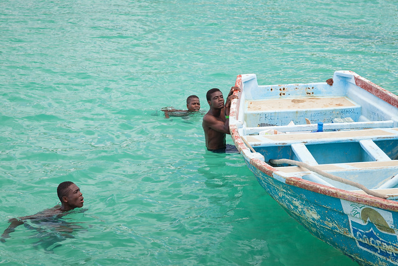 Boys swim out to inspect what we're doing as we're offloading supplies into a smaller boat to be taken ashore.