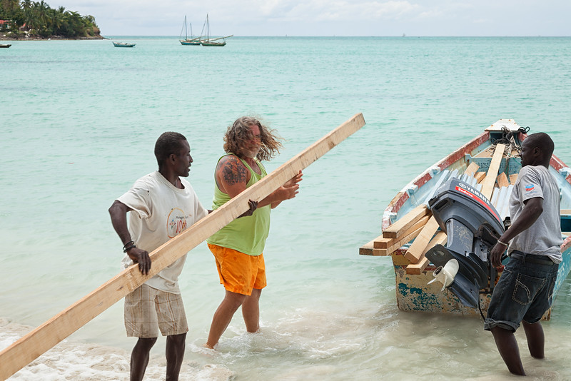 Unloading supplies from one of the boats after towing it to the other side of the island.