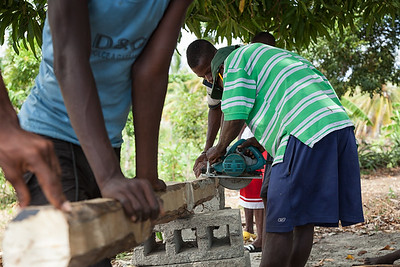 Sawing posts to be used for the hen house in La Hatte.