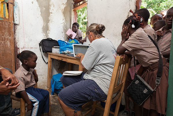 Children watch Emily input data into the computer during the health assessment at the temporary school.