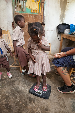 Children are weighed as a part of the health assessment at the temporary school in La Hatte.