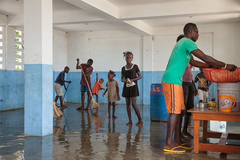 Children clean one of the classrooms after breaking the lock on the door.  They were also able to get access to the cistern, which had quite a bit of water in it.