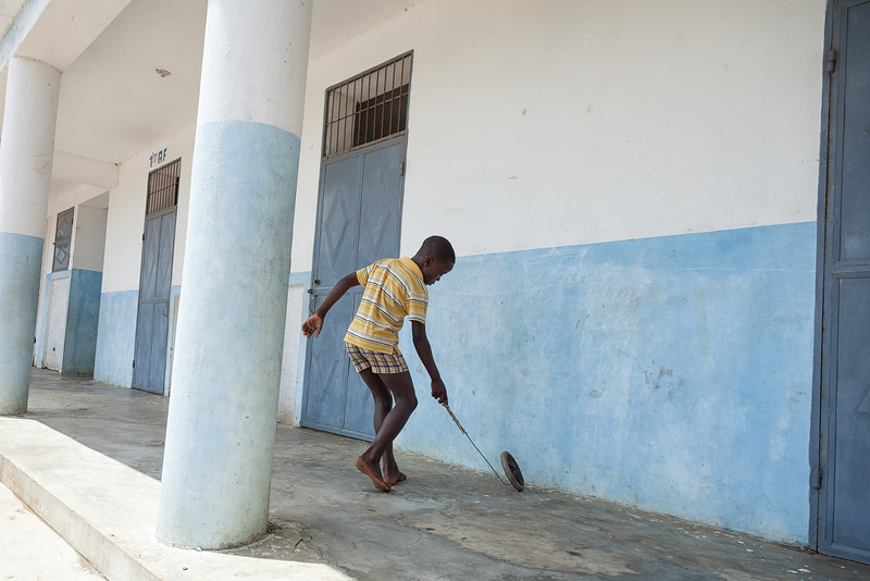 One of the schoolboys playing in front of the classrooms.
