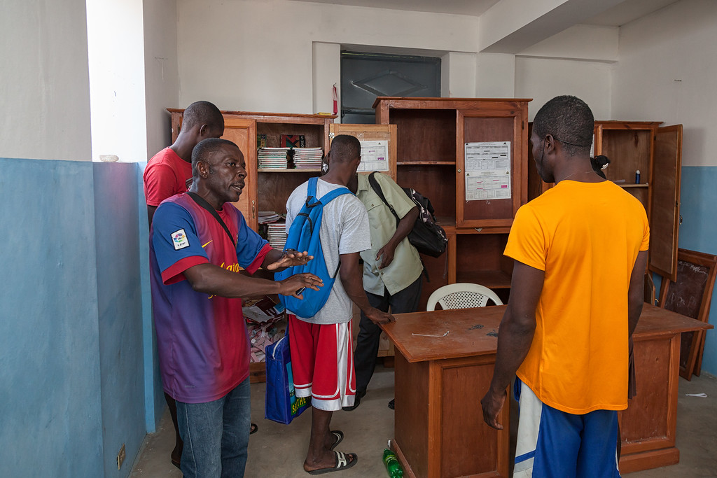 Nestor, head of the microcredit program, discusses what to do with supplies left in the school office.