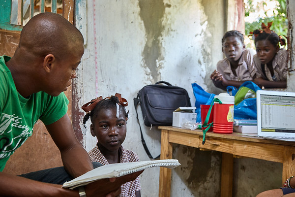 Sam, one of the local interpreters, asks one of the schoolgirls questions for the health assessment.