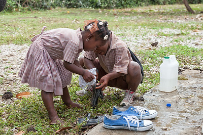 A strong rain had come through the night before and the mud is unbelievable.  Children clean their shoes and feet before class.