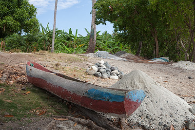 A typical scene on the beaches of Ile A Vache - small canoe, sand for cement, rocks for construction, and piles of fishing net.