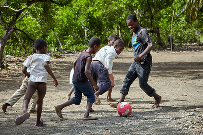 Boys playing a pickup soccer game.  The goal posts are different each day I walk past the field.