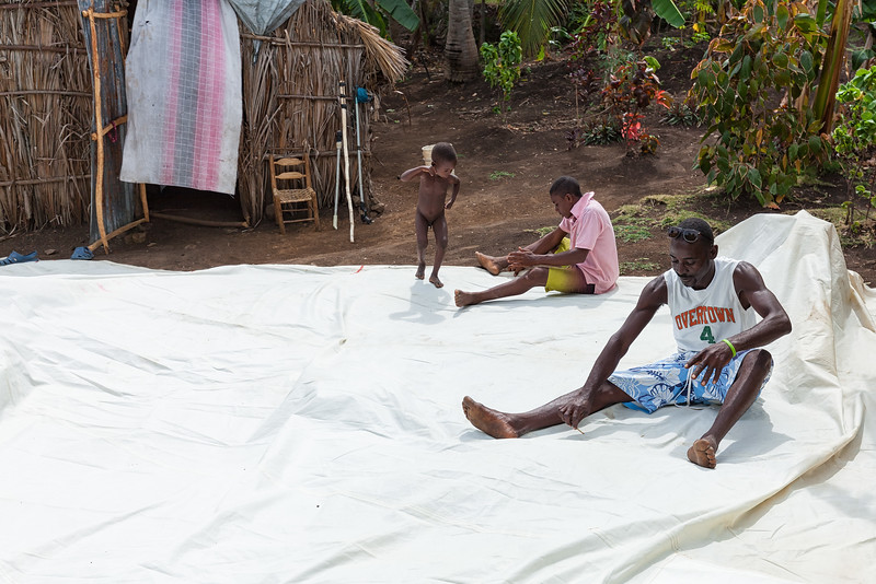 Fishermen in La Hatte working on one of the donated sails.  They'll cut and prepare them to fit on their boats.