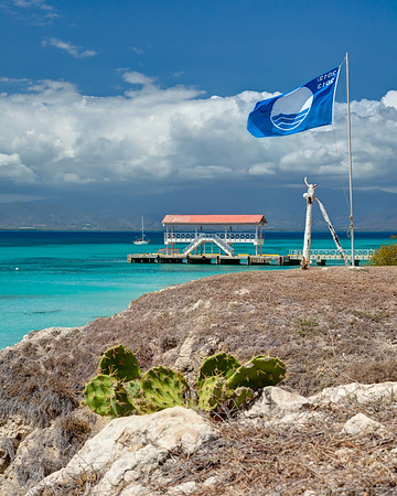 Looking towards Ponce from Playa Pelicanos on Isla Caja de Muertos Nature Reserve.  The ferry dock has service from Ponce.  The Blue Flag is an international eco-award giving to beaches with exceptional water quality, environmental education & management, and safety standards.