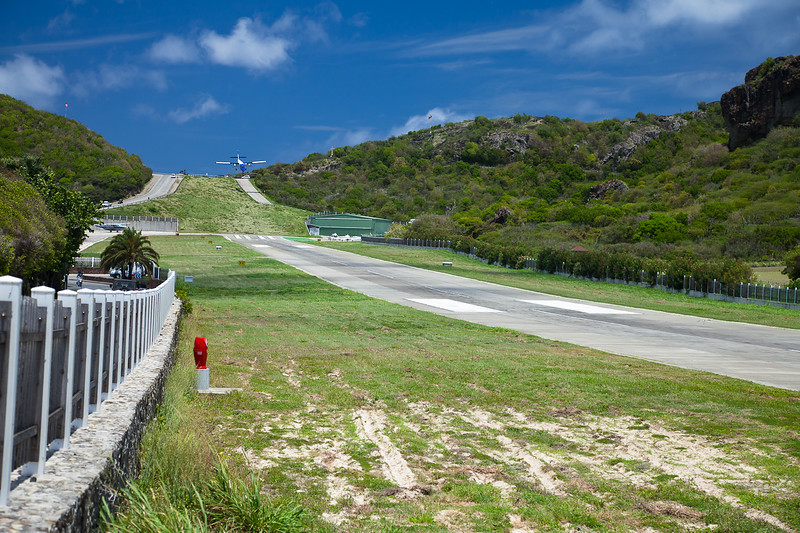 An aircraft flies over and down the hill leading into the Gustavia airport