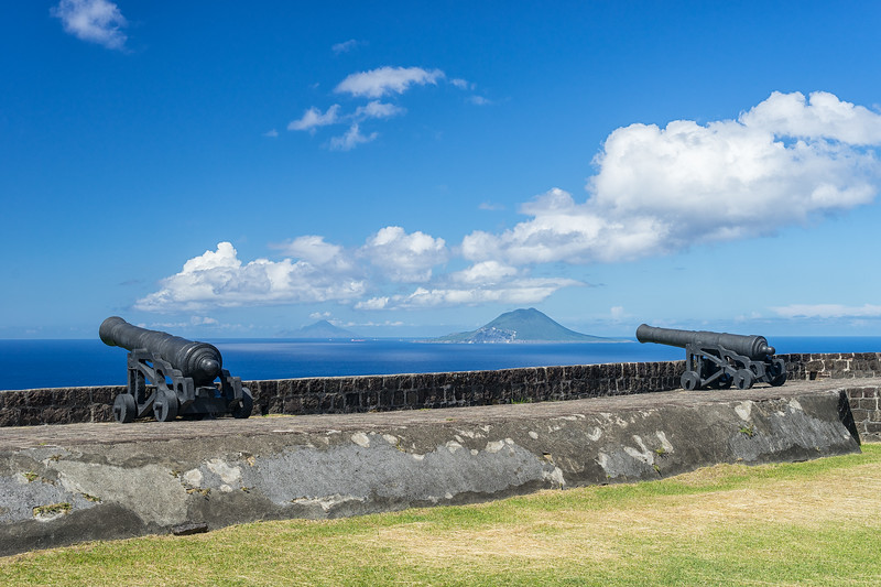 Cannons at the Western Place of Arms at Fort George.  St. Eustatius (near) and Saba (far) in the distance.  Note the reflection of the clouds on the water.