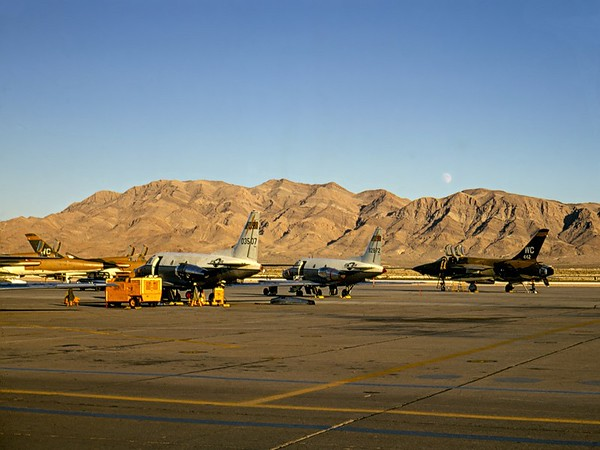 "Moon Over Nellis<br /> F-105 ""Thunderchiefs"" (""Thuds"") and two of the TWA aircraft.<br /> (""Teenie Weenie Airlines"") (T-39 Saberliners used for crew training)<br /> <br /> Nellis AFB, Nevada 1969"