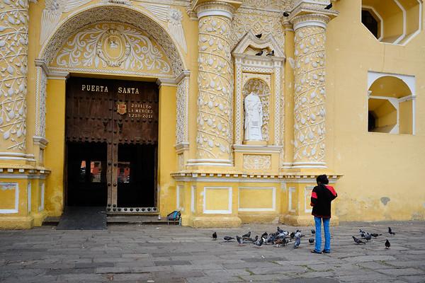Pigeon feeding in front of Iglesia de la Merced in Antigua Guatemala