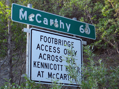 """Gunshot graffite"" adorns the sign at the beginning of the McCarthy Road."