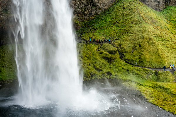 Tourists walking the trail behind Seljalandfoss waterfall