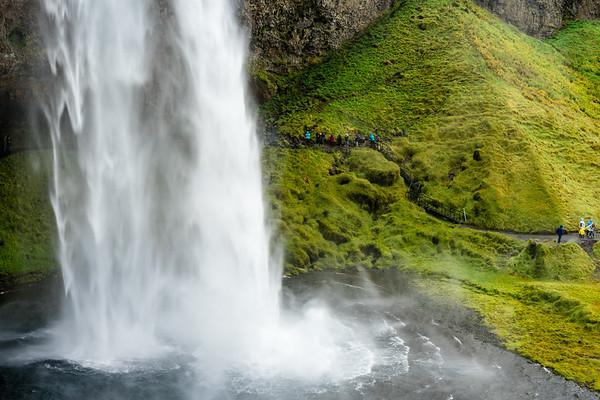 Tourists walking the trail behind Seljalandfoss waterfall