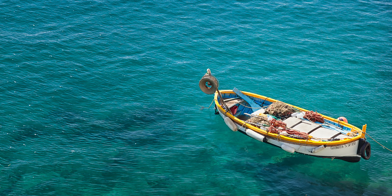 A small fishing boat waits tied up to the pier at Monterosso al Mare