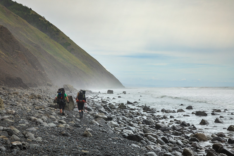 Backpackers making their way through a narrow rocky section of the Lost Coast Trail at low tide.