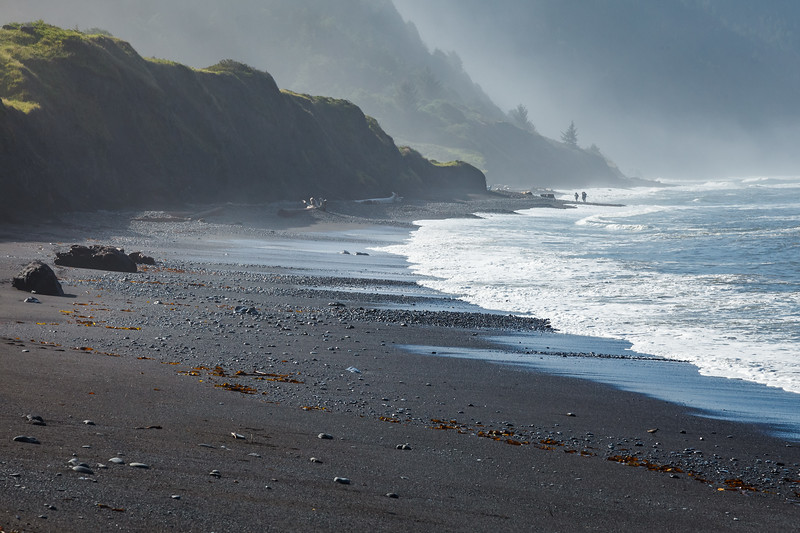 Backpackers navigate a narrow section of the Lost Coast Trail, approaching Shelter Cove.