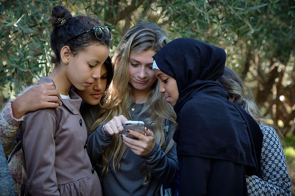 Moroccan children reviewing photos while on a photo walk with The Giving Lens.