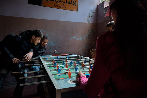 Children taking a break from photography lessons to play foosball before lunch.