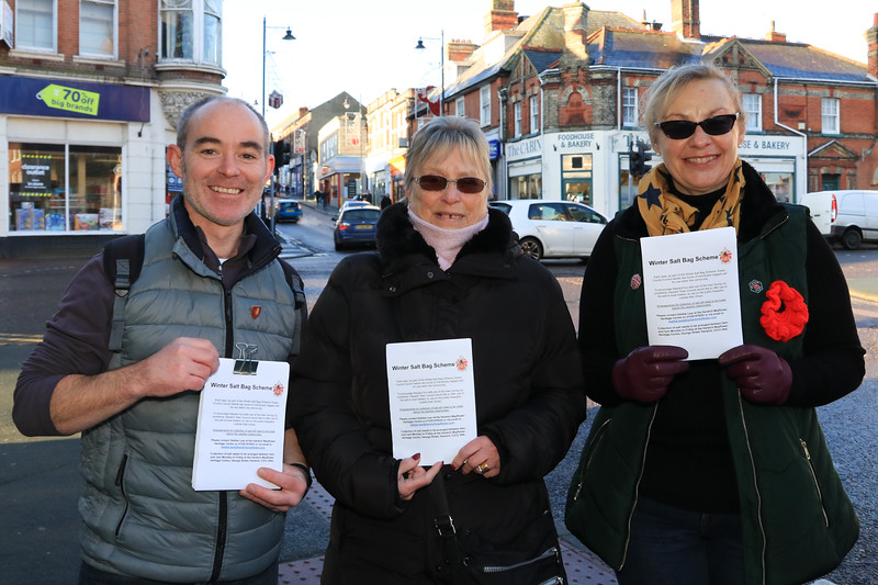 """30 NOV 2019 – L-R: Cllr. Sean Fay, Cllr. Margaret Saunders and  Cllr. Tanya Ferguson, – Harwich Town Council, Winter Salt Bag leaflet drop – Photo Copyright © Maria Fowler 2019<br /> <br /> Press release<br /> <br /> Traders given opportunity to keep pavements safe<br /> <br /> Harwich Town councillors have been visiting businesses in Dovercourt Town Centre and Historic Harwich to make local traders aware that supplies of salt will be available to them throughout the winter months should they wish to keep the pavements in front of their businesses ice free.<br /> <br /> Essex County Council runs a 'Winter Salt Bag' scheme under which they make supplies of salt available to Town and Parish councils to assist during icy conditions and Harwich Town Council, in partnership with the Harwich Mayflower Heritage Centre which stores the salt, uses its supply to assist businesses in Harwich and Dovercourt.<br /> <br /> Cllr Maria Fowler, who chairs Harwich Town Council's Environment and Community Committee, says <br /> <br /> """"As there is a limited salt supply the committee felt that it was best used to improve access to shops and businesses during icy conditions.  This being the case we make it available to local traders for use outside of their businesses.""""<br /> <br /> Harwich Town Council has produced a leaflet to publicise this opportunity and councillors have been out delivering the leaflet to businesses so that they know where the salt is and how they can get it.<br /> <br /> """"Harwich Town Council participates in this scheme to allow local businesses to help keep open and accessible in icy conditions,"""" continued Maria Fowler.  """"By delivering this leaflet we are making sure that local traders are aware that supplies of salt are available to them."""""""