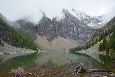 The mountains behind Lake Agnes covered in clouds