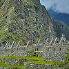 Stone houses in Machu Pichu with Huaynapicchu in the background.