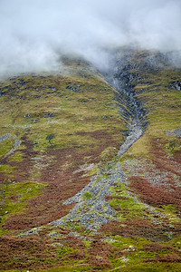 Sheep graze high up on the slopes of Beinn Dorain, as low clouds obscure the top.  Scotland.
