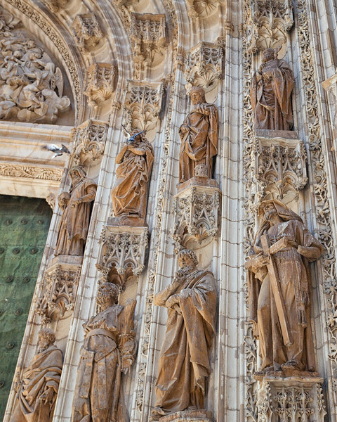 Pigeons flee from the statues surrounding an entrance to Seville Cathedral, Spain.