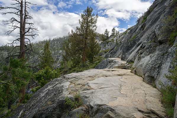 The trail to Cascade Falls alternates between wooded dirt paths and open granite pathways.