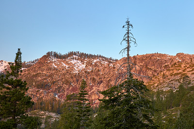 The granite cliffs on the Five Lakes Trail hike glow a pinkish-orange in the morning.