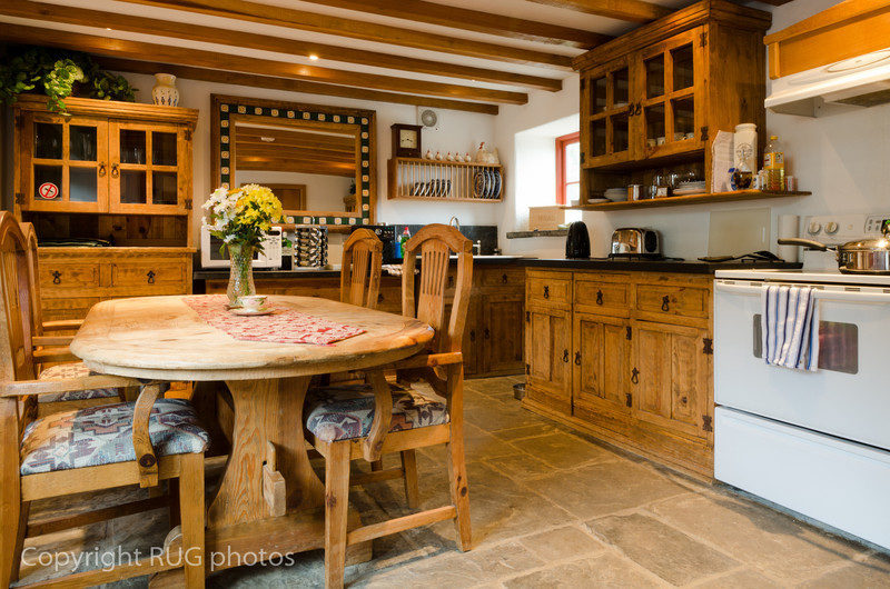 The eat-in Kitchen had a large scrubbed pine table and chairs, together with freestanding dressers topped with thick blue-gray Welsh slate worktops. The range style cooker was impressive!