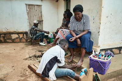 Young men provide manicures and pedicures for women during X-SUBA's celebration of International Women's Day.  This holiday is taken very seriously in Uganda and activities like this take place all over the country.