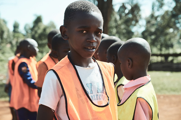 A participant in a school soccer tournament in Walukuba, wearing one of X-SUBA's provided bibs.